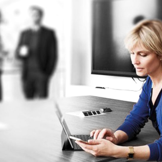 Blonde woman watching her phone in a meeting room